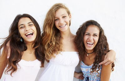 Three brunette teenage girls holding each other and laughing