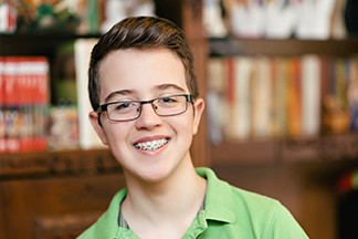 Young smiling boy wearing a green shirt, glasses and braces.