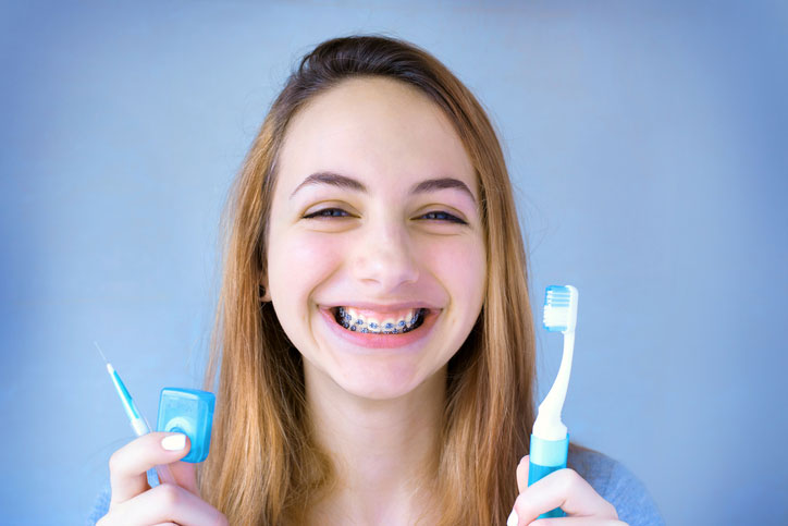 Pre-teen girl with braces smiling and holding a toothbrush, floss, and an interdental toothbrush.